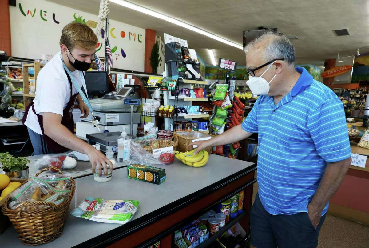 Cashier Eric Bacanskas, 18, left, of Walnut Creek, checks out customer Harry Kirsch, 64, of Lafayette, at the Pleasant Hill Market in June. While Contra Costa County plans to ease some mask rules on Nov. 1, people in shops must continue to mask up, most likely for several more months.
