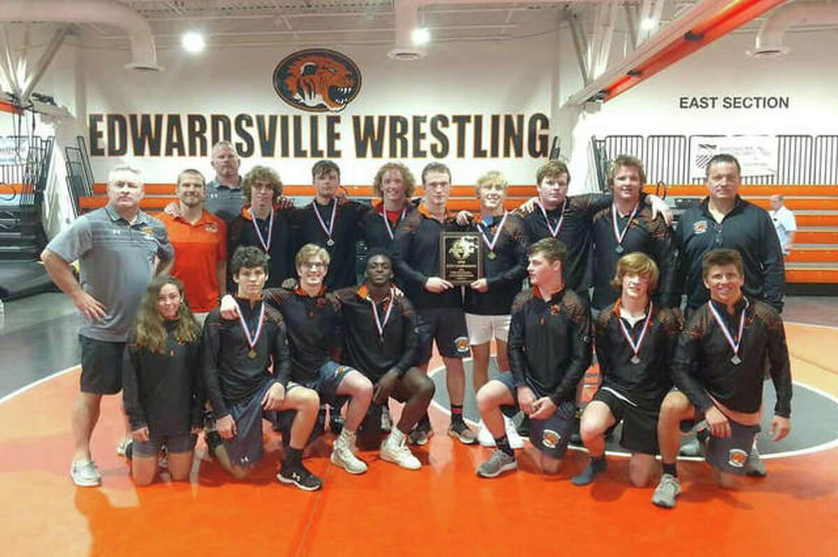 The Edwardsville Tigers pose with AAA Edwardsville Super Regional championship plaque after their team win on Sunday inside the Jon Davis Wrestling Center.