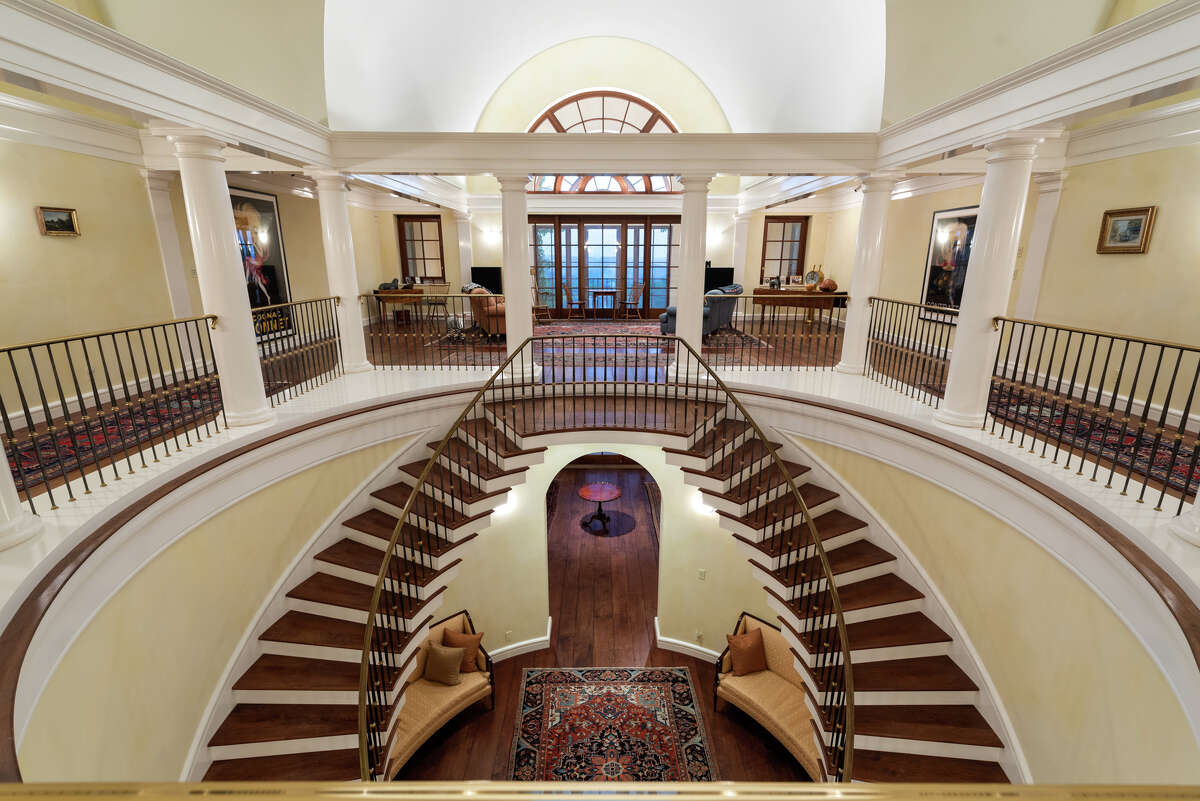 The home's foyer has a two-story double staircase that leads up to the second floor.