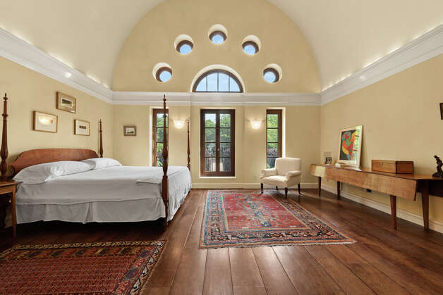 One of the five bedrooms in the home has high arched ceilings and windows that look out onto the wooded property. Photo: Dot Record Media