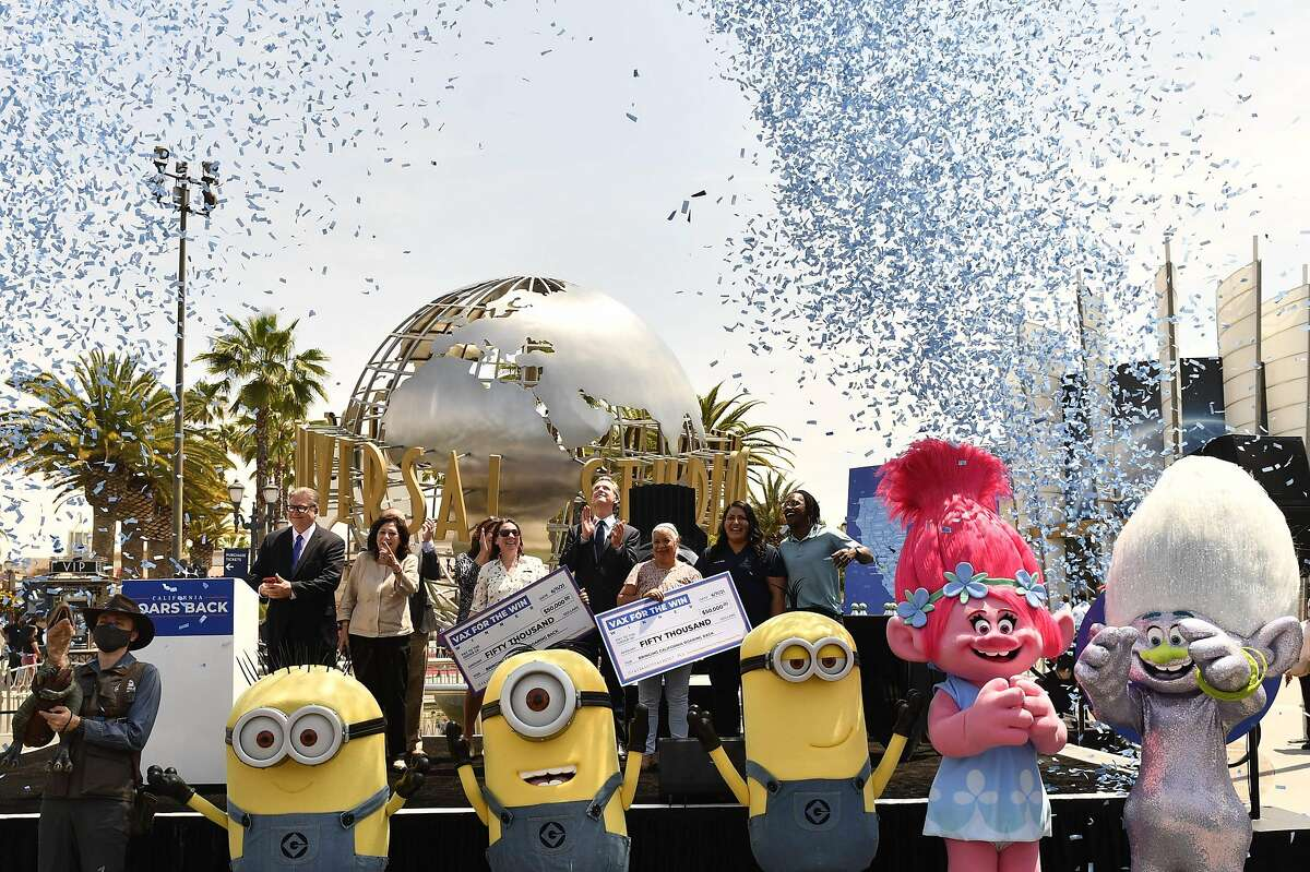 Gov. Gavin Newsom (center) presents ceremonial checks to winners of the California vaccination drawings at Universal Studios in Los Angeles on Tuesday.