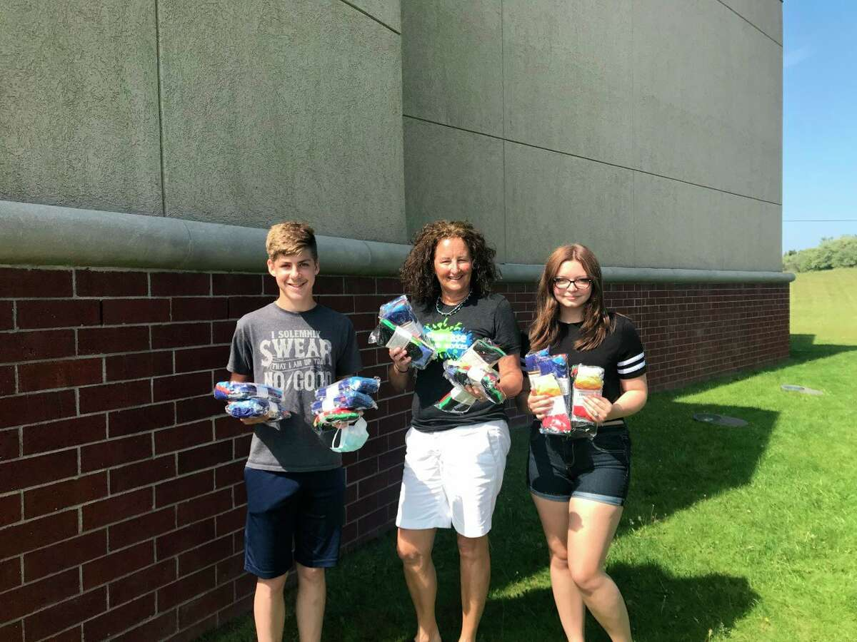 Rita McCann (center), from Staircase Youth Services of Manistee County, poses for a photo with Manistee High School band students Damien McEntaffer and Brandi Monroe. The Manistee Area Public Schools band program donated socks from itsBand Boosters virtual sock fundraiserto Staircase. (Courtesy photo)