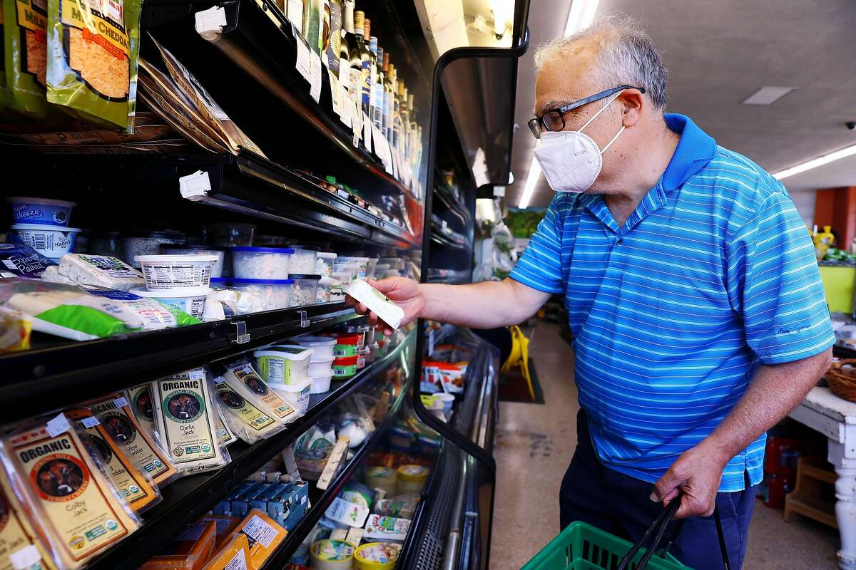 """Harry Kirsch, a Lafayette resident, shops for cheese at Pleasant Hill Market. """"I hope it's the last step back to normal,"""" Kirsch said about reopening day."""
