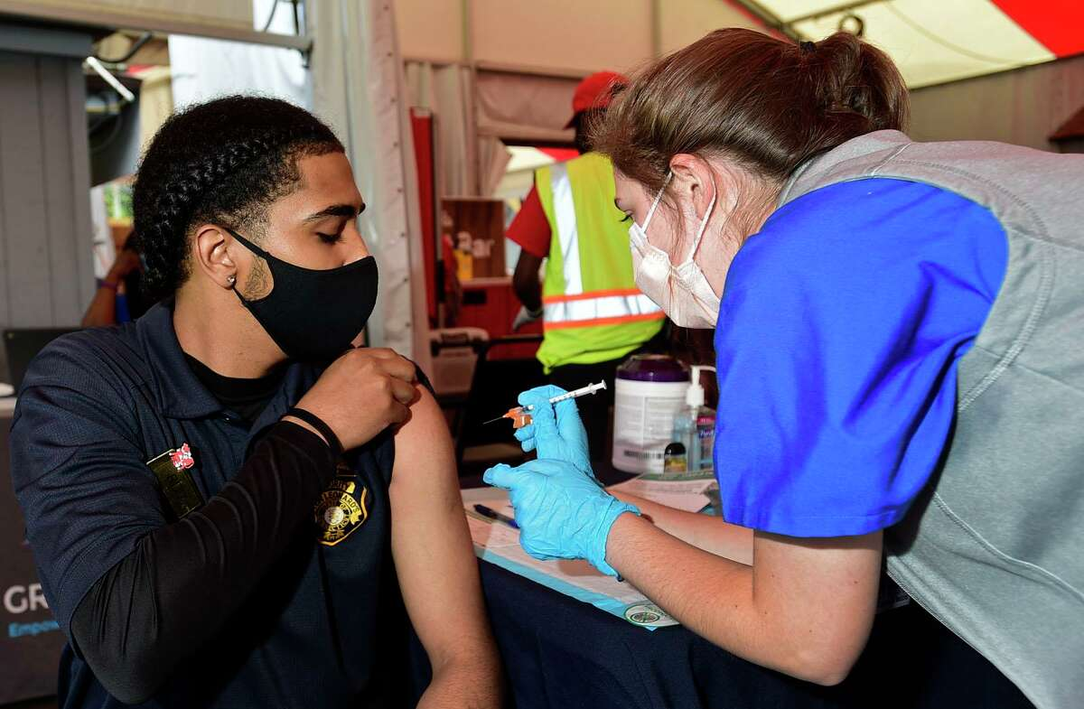Emily Carrizzo adminsters the shot to Stew's security guard Rod Candelario during the Griffin Hospital COVID-19 vaccination clinic at Stew Leonard's flagship store Tuesday, June 15, 2021, in Norwalk, Conn. The free clinic is open to the public and continues Wednesday, June 16, 2021, at the Norwalk store.