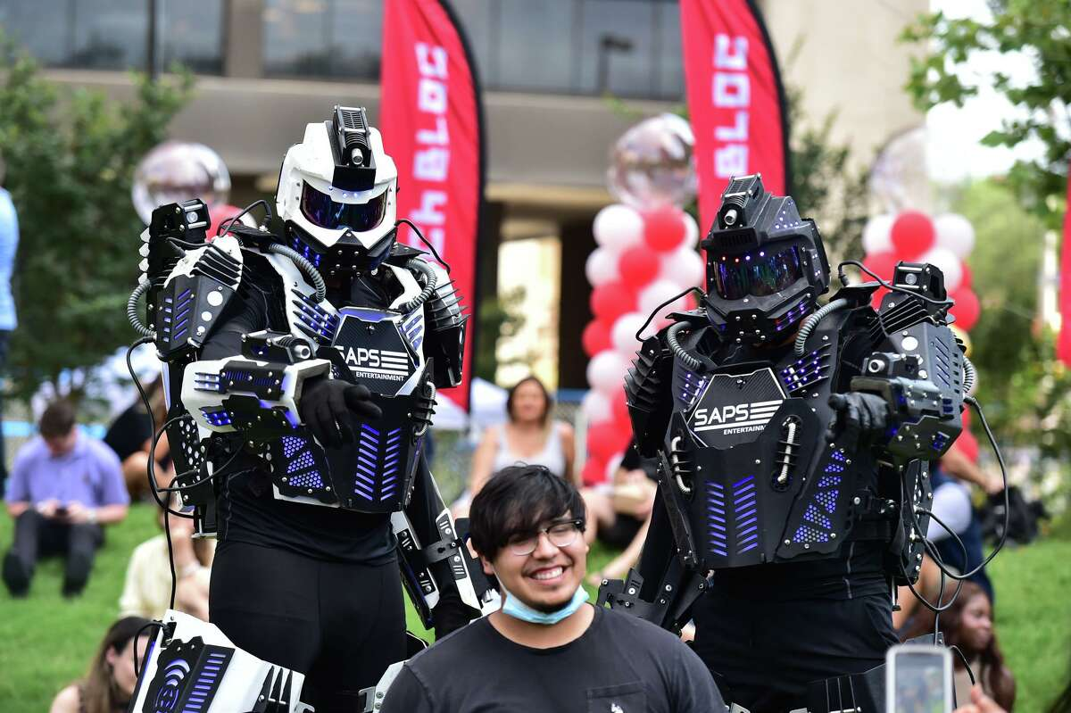 Aaron Rodriquez poses with SAPS Robots during a reboot rally hosted by Tech Bloc at the Weston Urban Legacy Park downtown Thursday evening.