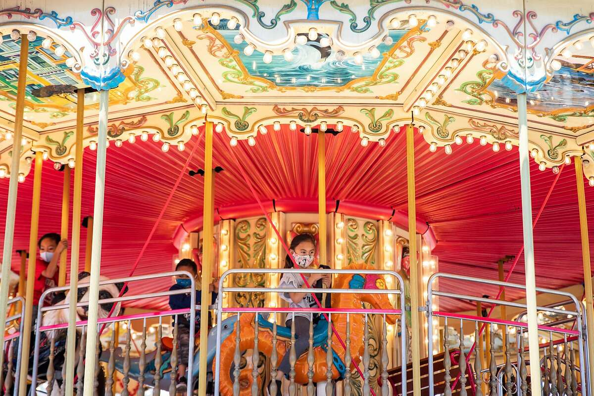 (Fom left) Jack Robinson, 7, Dom Robinson, 5, and Gianna Robinson, 9, wear masks before choosing a seat on the carousel at Pier 39 on the first day of lifted COVID-19 restrictions in San Francisco, Calif. Tuesday, June 15, 2021. California lifted nearly all of its pandemic restrictions at 12:01 a.m. on Tuesday, June 15, a date marking a key milestone in reopening efforts for the state and the San Francisco Bay Area.