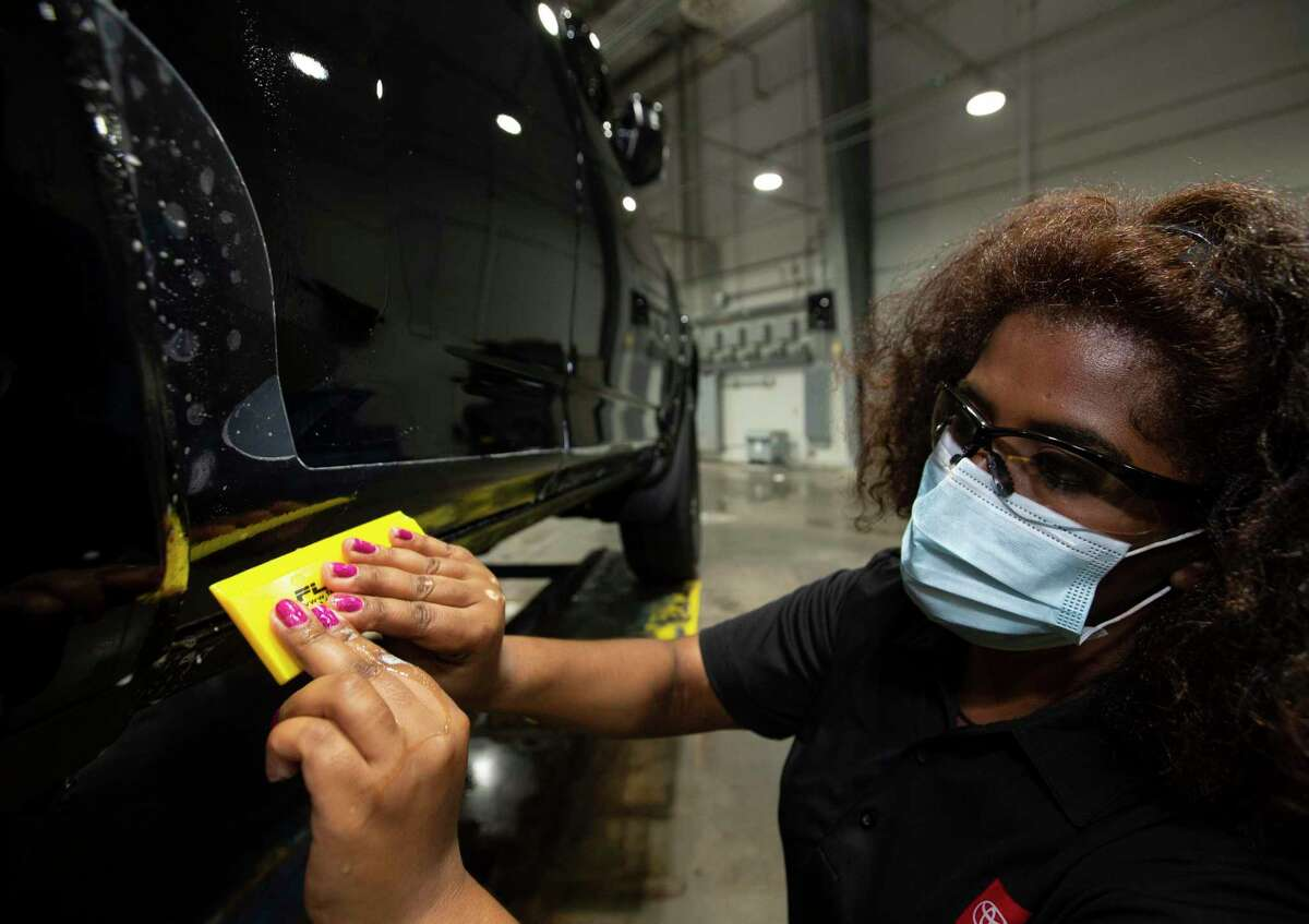 Gulf States Toyota visual installer Tigist Haile putting protective films onto a 4Runner at the vehicle processing center Wednesday, May 26, 2021, in Houston.