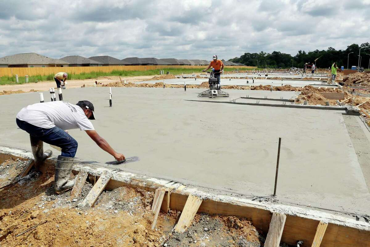 Construction workers put down concrete foundations for new houses of LGI Homes along Sunshine Meadow Drive in a new section of the Bauer Landing sub-division Thursday, June 3, 2021 in Hockley, TX.