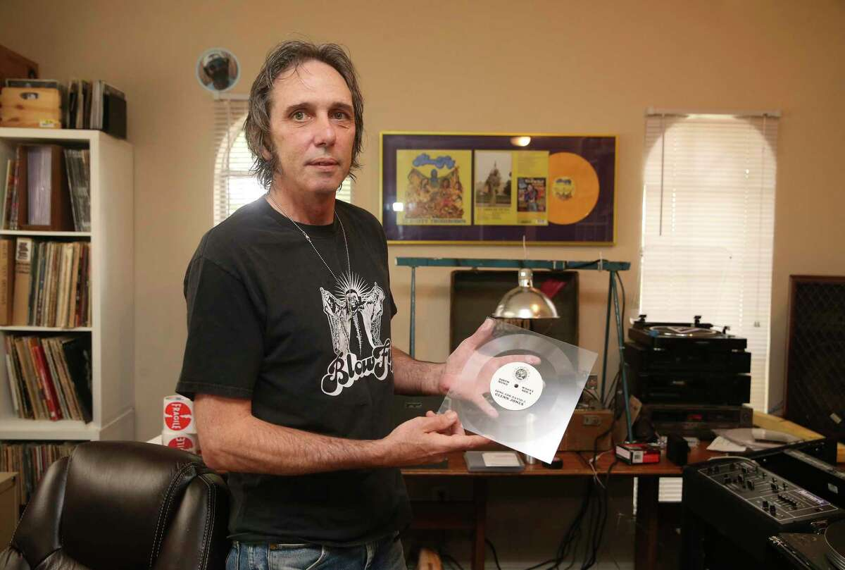 """Jeff Smith holds what he calls, """"a mono sound artifact,"""" lathe cut of a song dedicated to the late Davy Jones, at his house studio, Friday, June 11, 2021. Smith is the owner of Saustex Records and is also the singer for, """"Hickoids,""""a cowpunk band. Jones was the guitarist on the band and died of cancer in 2015. The song was written and performed by Jones'brother, Glenn Jones."""