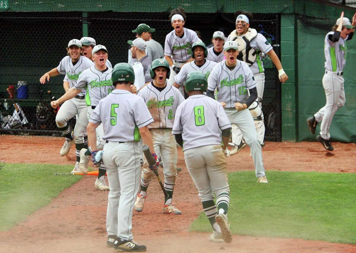 After a single by Norwalk's Konstantinos Kodonas, teammates rush to celebrate a run brought in by Noah Maldonado (8) during the Class LL state championship game against Westhill on Saturday at Palmer Field in Middletown.