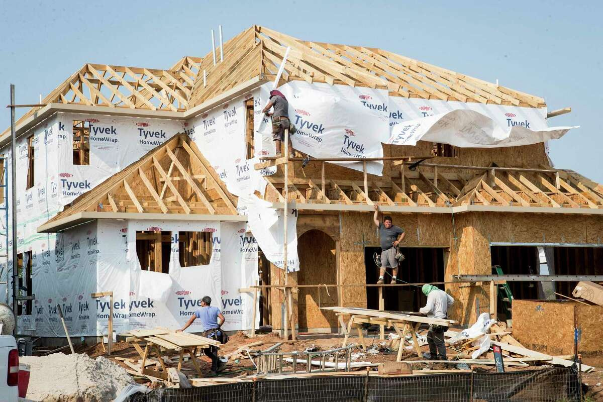 Housing starts rose by 20.3 percent over the year to 36,739 in the Houston area in 2020, according to Zonda. Construction workers build a home the Sienna development in Missouri City.