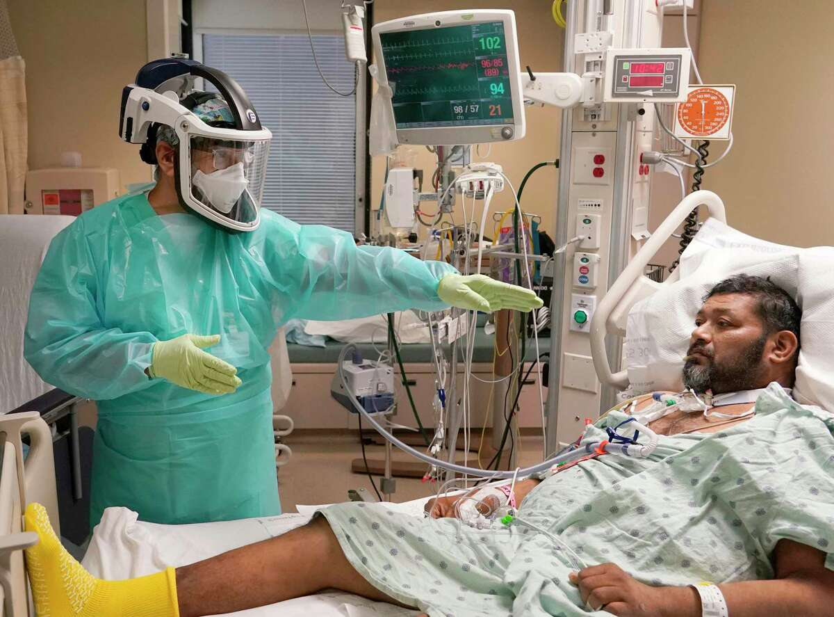 Carlos Martinez, a physical therapy technician, works with COVID-19 patient, Jose Gil Suarez, in the MICU at Houston Methodist Hospital Monday, Dec. 21, 2020 in Houston.