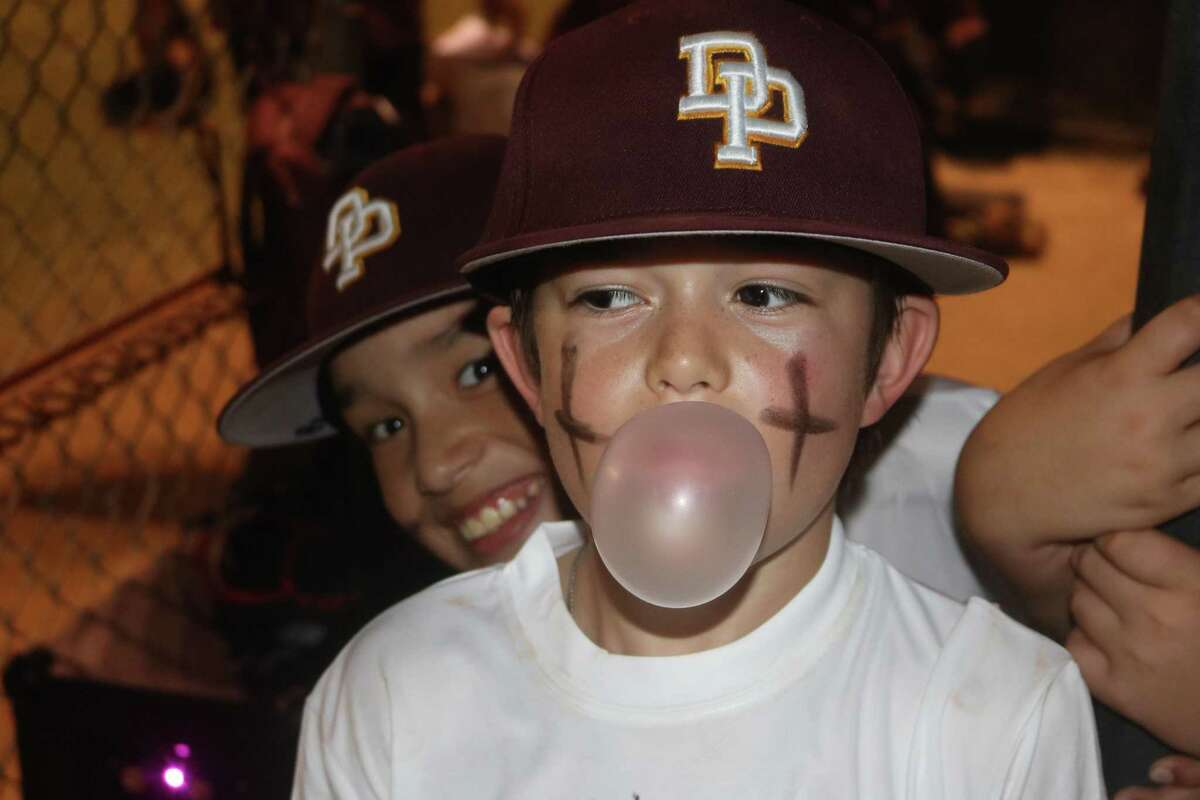 Deer Park Mustang all-star Aysen Miller works on his bubble-blowing skills Monday night after he and his teammates built a comfortable lead in the Directors Tournament championship game at Friendswood's Renwick Park.