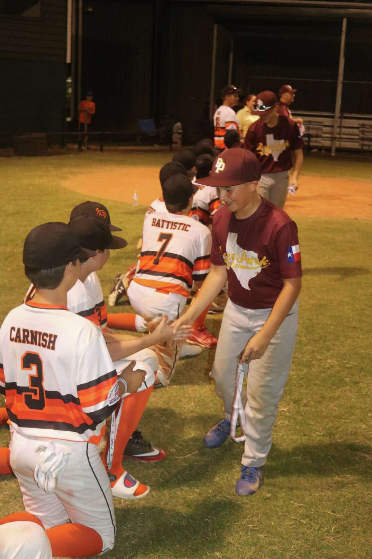 Members of Deer Park's Bronco all-star roster congratulate La Porte players during postgame ceremonies Monday night at Friendswood's Renwick Park.