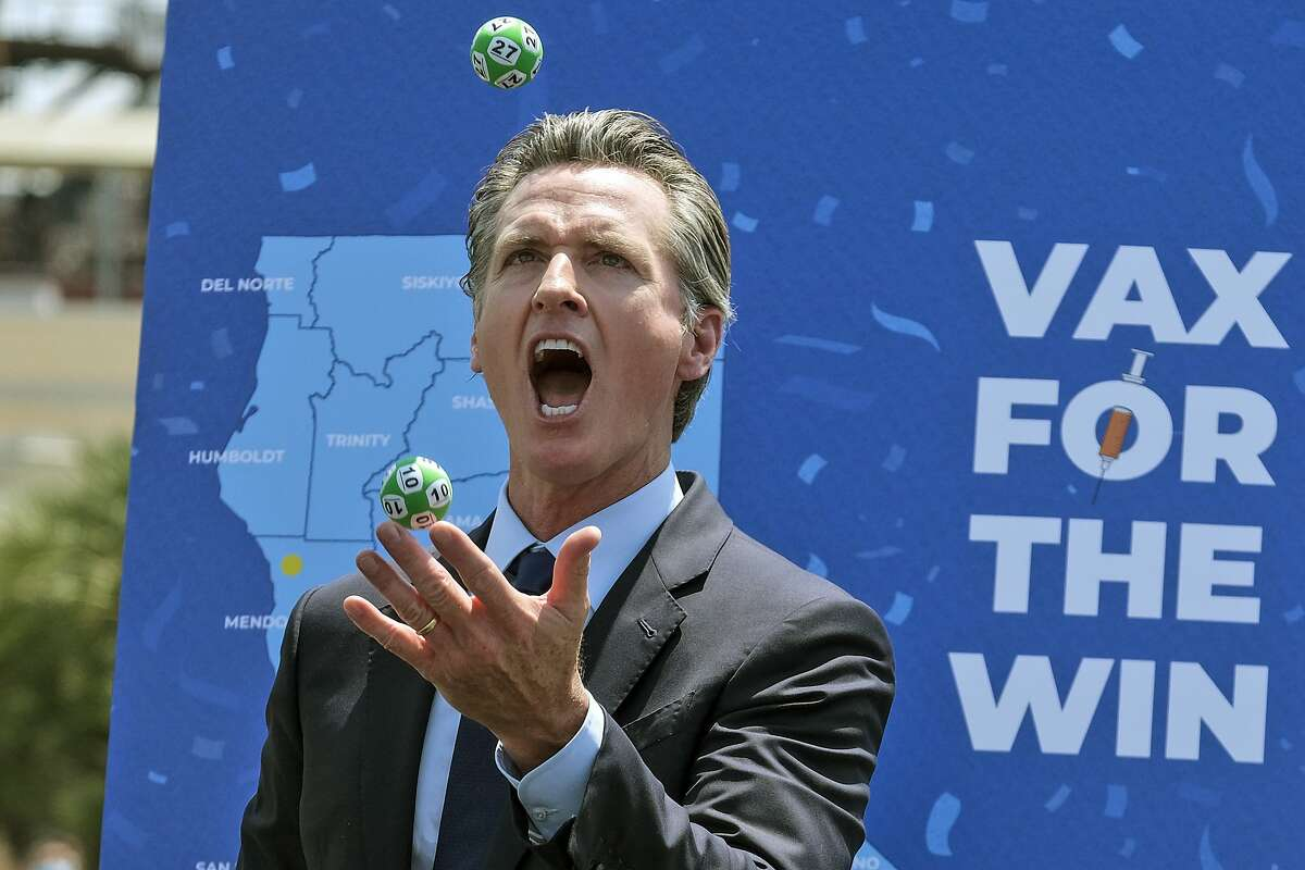 Gov. Gavin Newsom juggles balls with winning numbers after a lottery drawing for vaccinated people Tuesday at Universal Studios in Los Angeles.