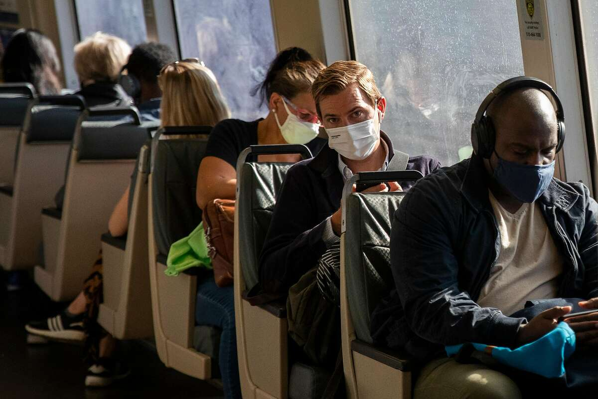 Morning commuters wear masks while riding a San Francisco-bound train at MacArthur Station in Oakland. Masks are still required on public transit under California's reopening rules.