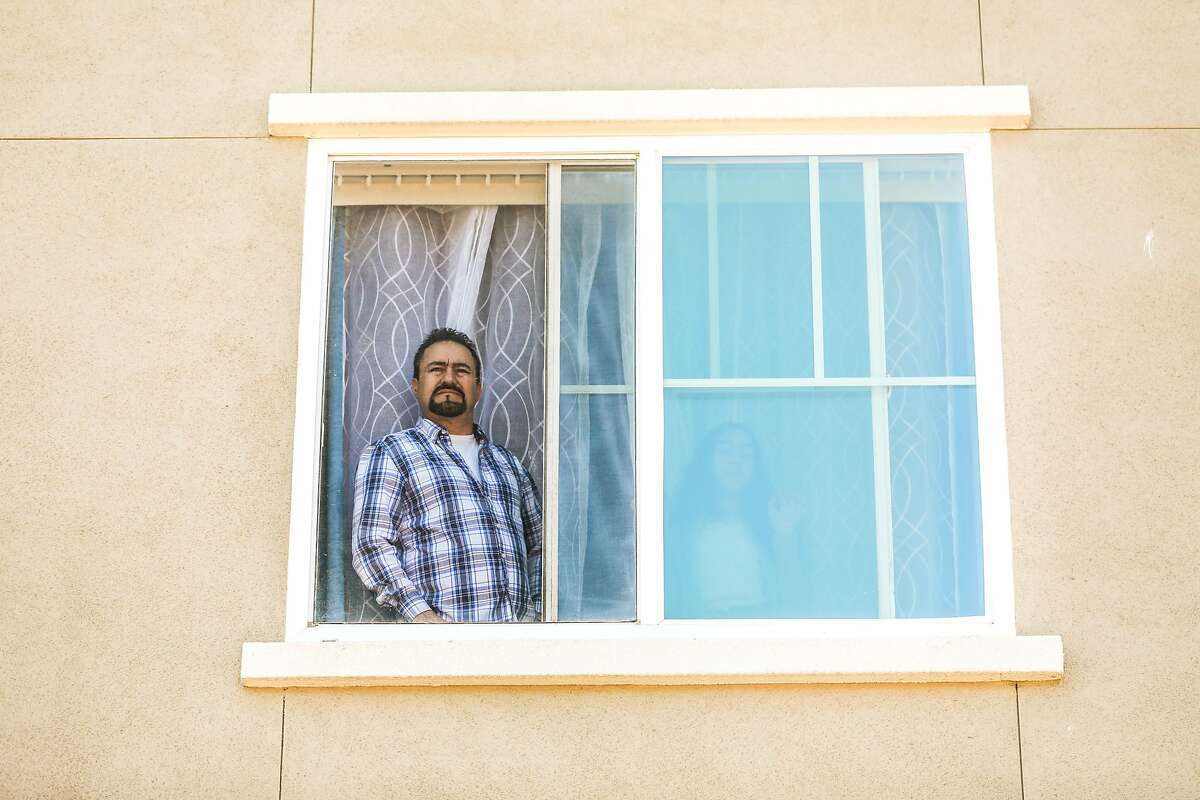 """A man watches the """"Reopening of the State Celebration"""" party from his window in Colma. The party was to celebrate the first day that vaccinated people could move around both indoors and outdoors without masks."""