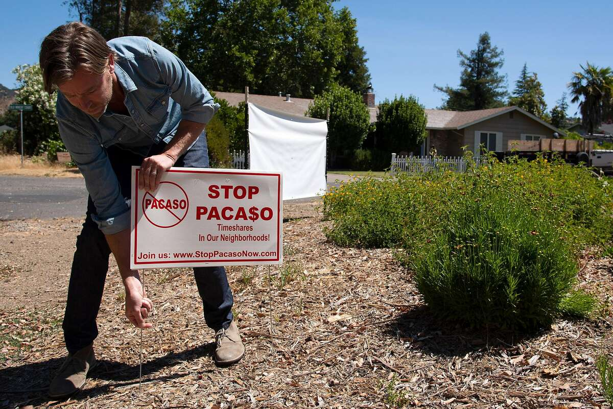 Brad Day places an anti-Pacaso sign at the corner of his Sonoma cul-de-sac in protest to the start up company's actions in his neighborhood.