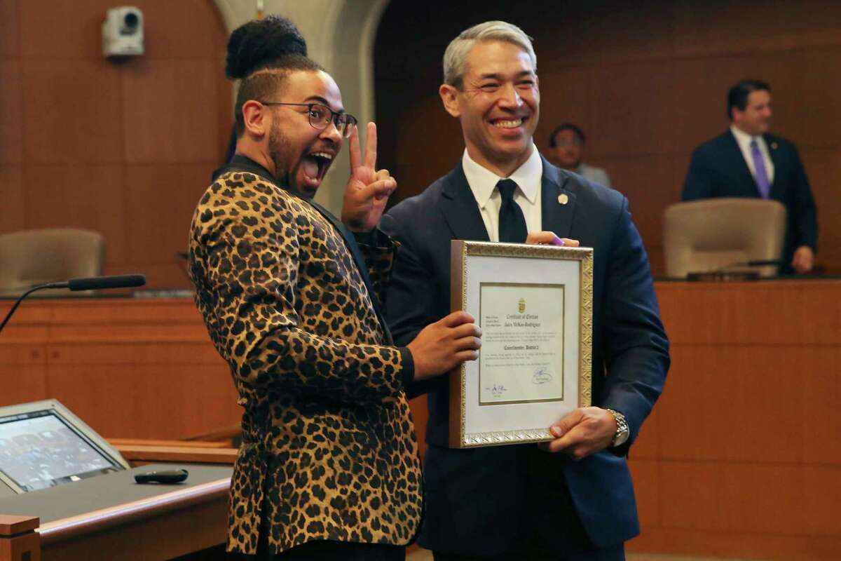 Newly elected San Antonio District 2 City Council member Jalen McKee-Rodriguez, left, reacts after receiving his Certificate of Election from Mayor Ron Nirenberg during a swearing-in ceremony in Chambers, Tuesday, June 15, 2021.