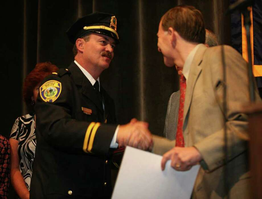 Fairfield's new deputy chief Christopher Lyddy, left, is congratulated by First Selectman Kenneth Flatto after being sworn in during a ceremony at the Ludlowe Middle School auditorium on Monday, September 13, 2010. Photo: Brian A. Pounds / Connecticut Post