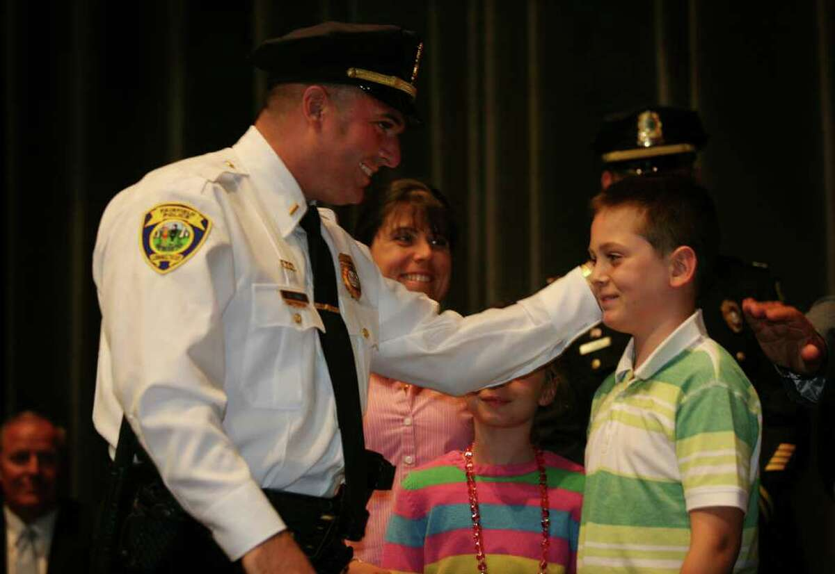 New lieutenant Christopher Tursi smiles at his son Kyle, 9, after having his badge pinned on during a ceremony at the Ludlowe Middle School auditorium on Monday, September 13, 2010.