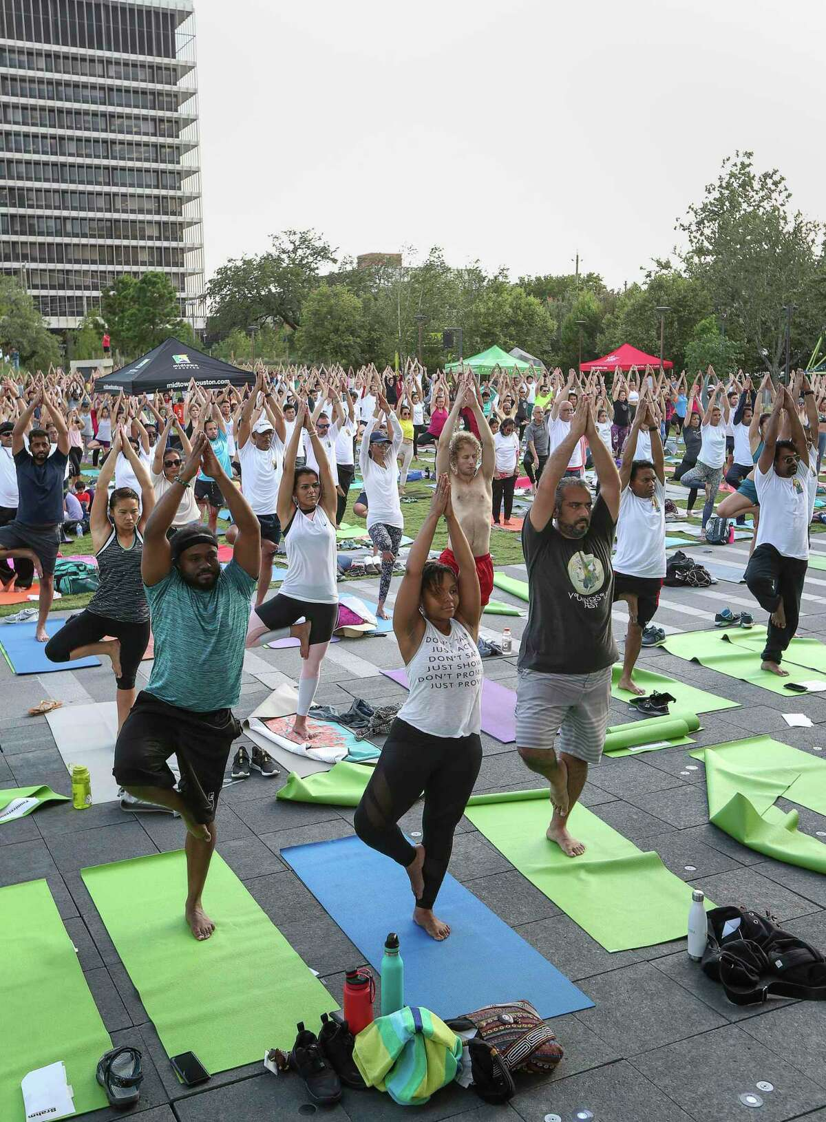 People practice yoga during an International Day of Yoga event at Midtown Park on Friday, June 21, 2019, in Houston.