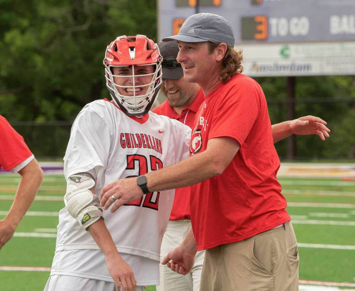 Guilderland's Daniel Macchiarella gets a hug from coach Sean McConaghy after defeating Shaker in the Class A boys' lacrosse final on Tuesday, June 15, 2021 in Amsterdam, N.Y. (Lori Van Buren/Times Union)