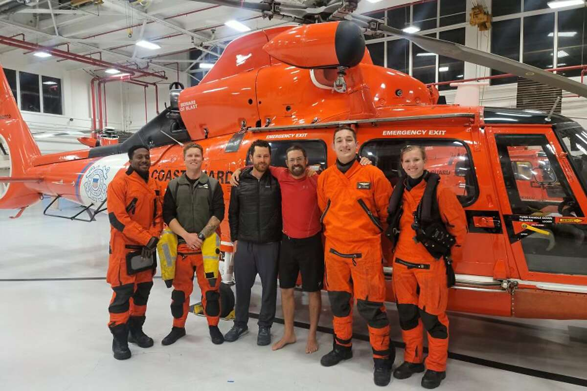 Kayaker Cyril Derreumaux (in shorts) with the Coast Guard helicopter crew that rescued him off the Santa Cruz coast on June 5.