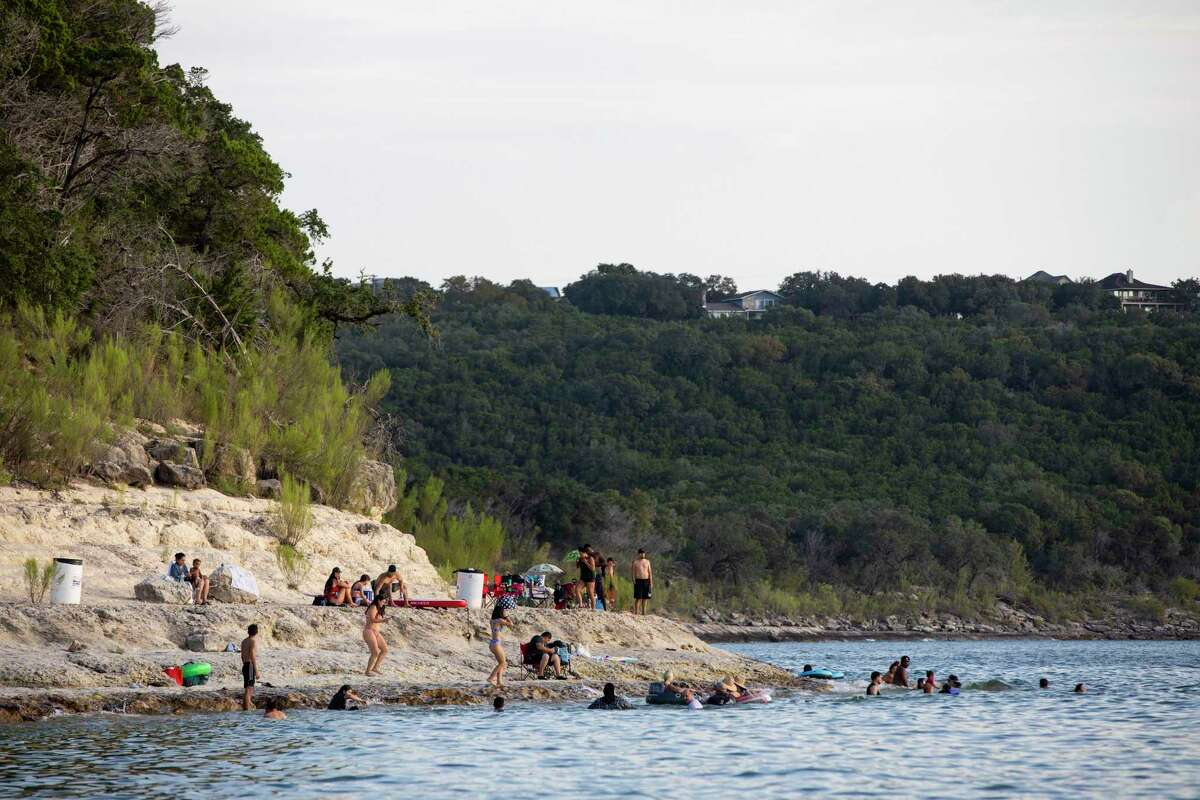People congregate on the shore of Canyon Lake in Spring Branch in this September photo. Late Sunday, Celestin Mc-angy was discovered 47 feet below the surface of Canyon Lake by members of the South Hays Fire Department dive team, police said.