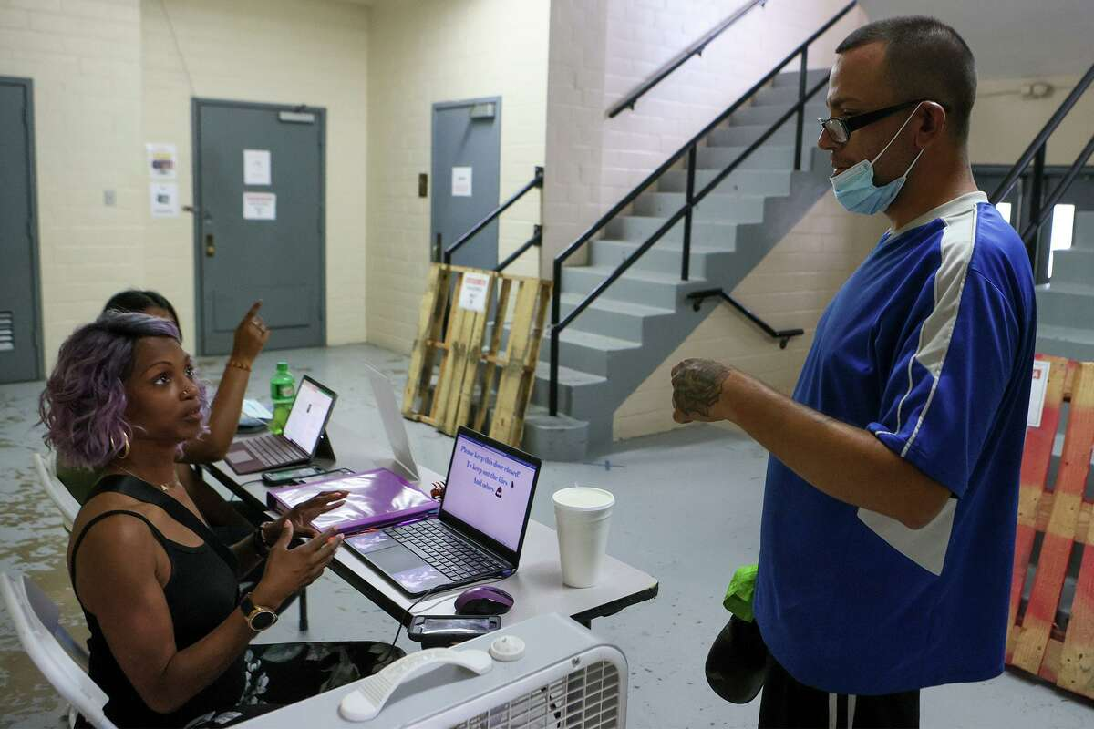 John Liveoak, right, checks in with community service specialist Tamicko Jones at the San Fernando Gym's cooling center at 319 W. Travis, where he went Tuesday to escape the heat outdoors.