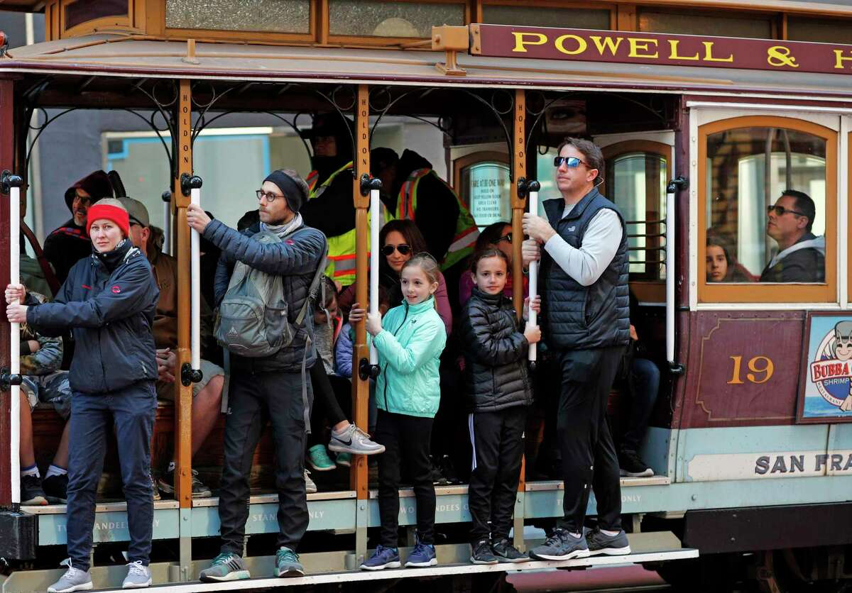 A family riding the world famous cable cars along the Powell Street line in San Francisco, Calif. Forced to close on account of the pandemic, the city's cable car service was ready to resume, officials said.