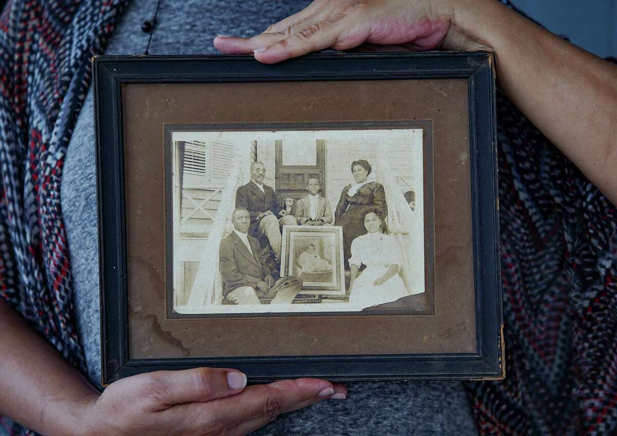 June Pulliam holds a photo of her ancestors sitting in front of the home she still lives in, in Galveston on Friday, May 28, 2021. Pulliam's family migrated to Galveston in 1865, when her great-grandfather, Horace Scull (top left in the photo) was five years old.