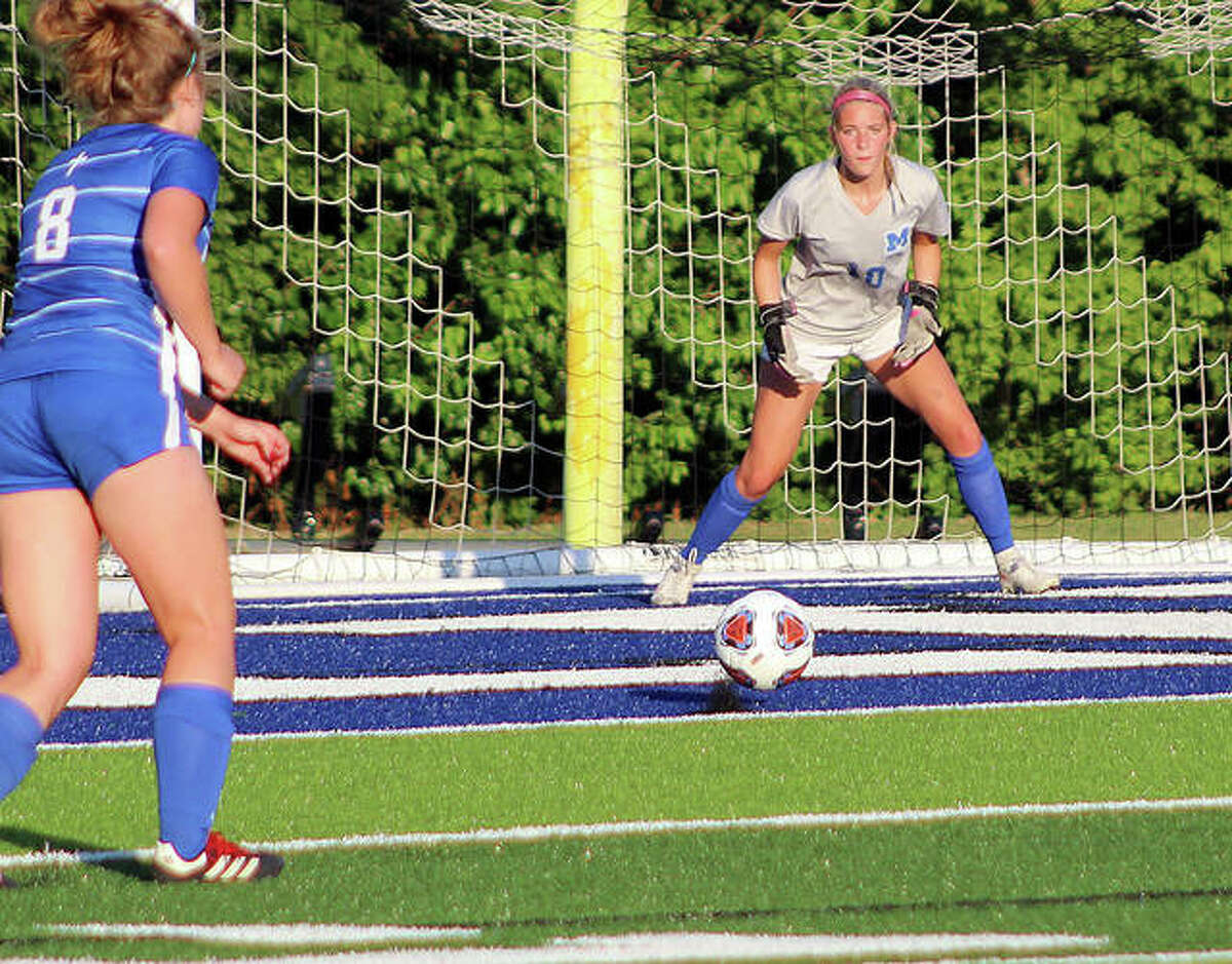 Marquette goalie Hannah Marshall keeps an close eye on the ball during Tuesday night's Class 1A Super-Sectional game in Columbia against Belleville Althoff. Teammate Haley Williams is shown at left.