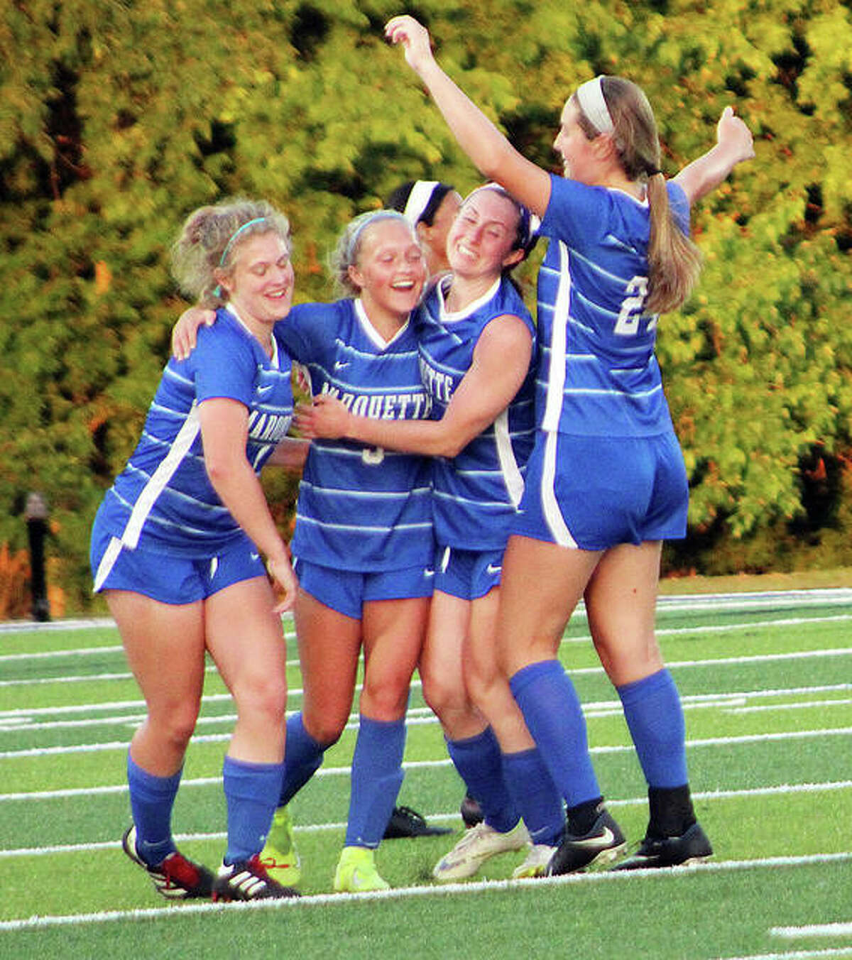 Marquette's Clare Antrainer, center, is surrounded by teammates as they celebrate her second-half goal in Tuesday's 1A super-sectional game against Althoff at Columbia.