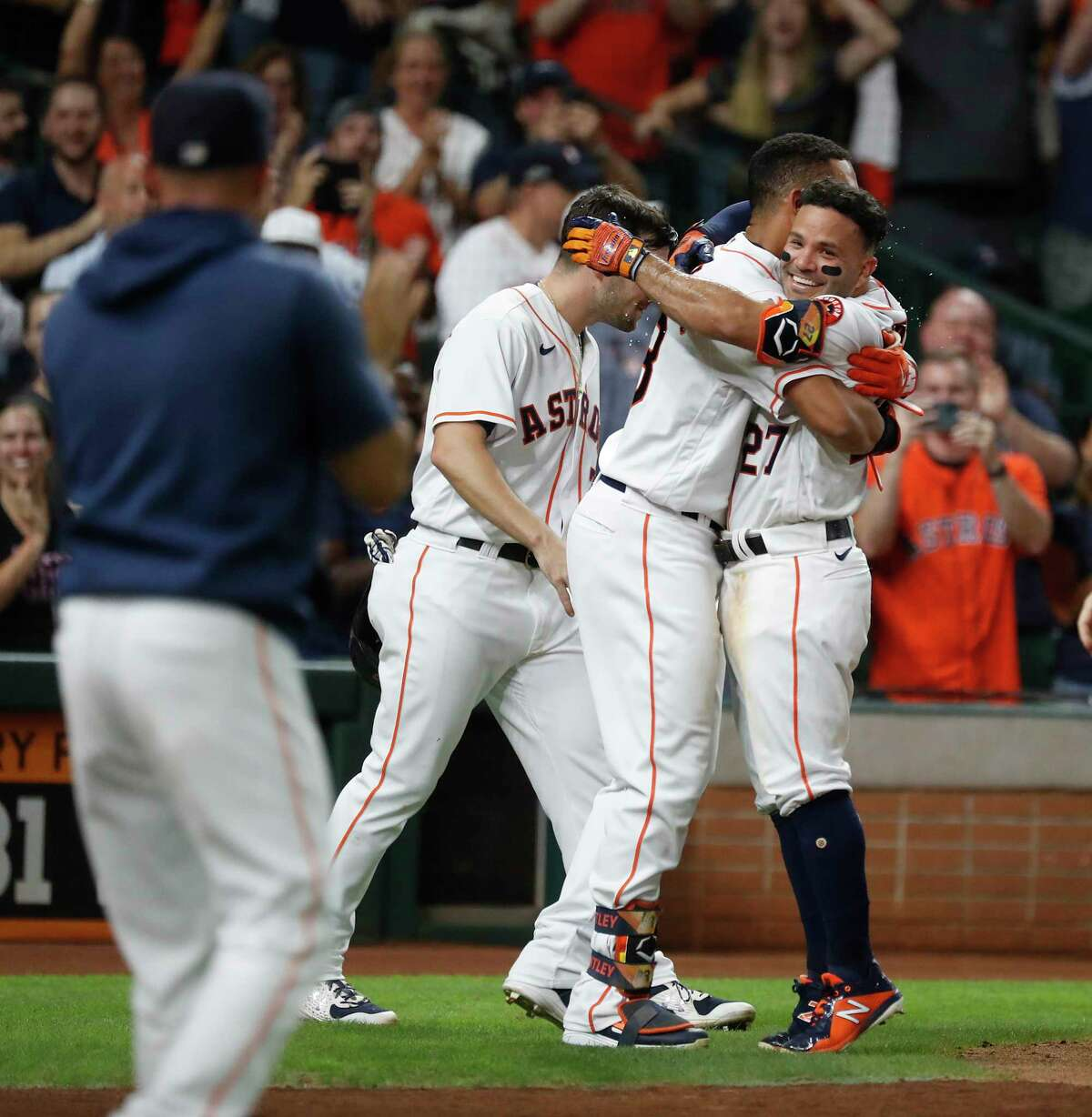 Jose Altuve (right) hugs Michael Brantley after he hit a walkoff grand slam during the 10th inning Tuesday.