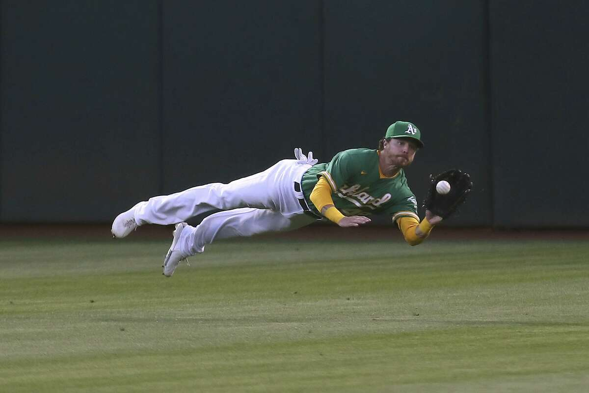 Oakland Athletics' Skye Bolt catches a ball hit by Los Angeles Angels' Jared Walsh during the sixth inning of a baseball game in Oakland, Calif., Tuesday, June 15, 2021. (AP Photo/Jed Jacobsohn)