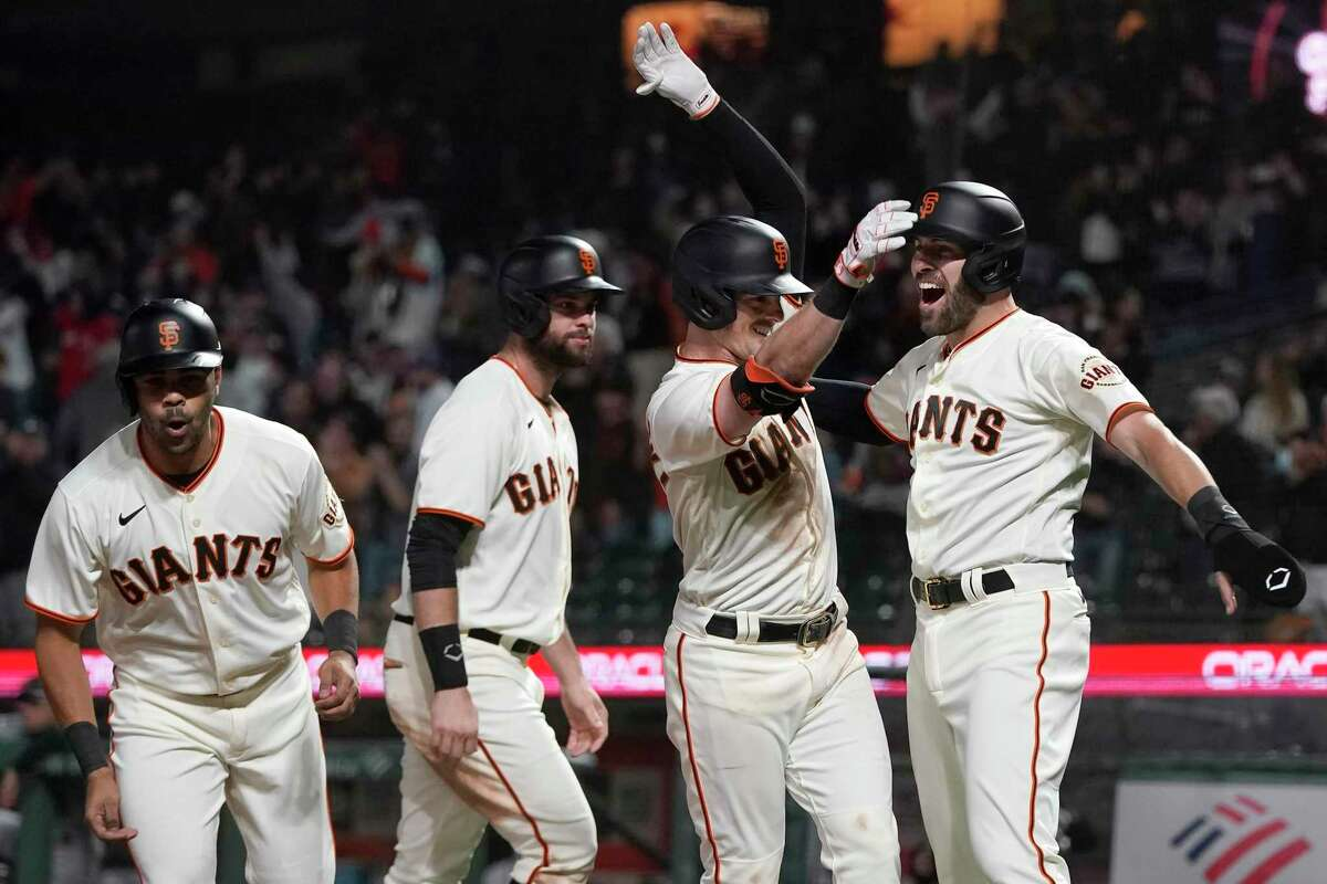 San Francisco Giants' Mike Yastrzemski, second from right, celebrates after hitting a grand slam home run that scored LaMonte Wade Jr., from left, Brandon Belt and Curt Casali during the eighth inning of a baseball game against the Arizona Diamondbacks in San Francisco, Tuesday, June 15, 2021. (AP Photo/Jeff Chiu)