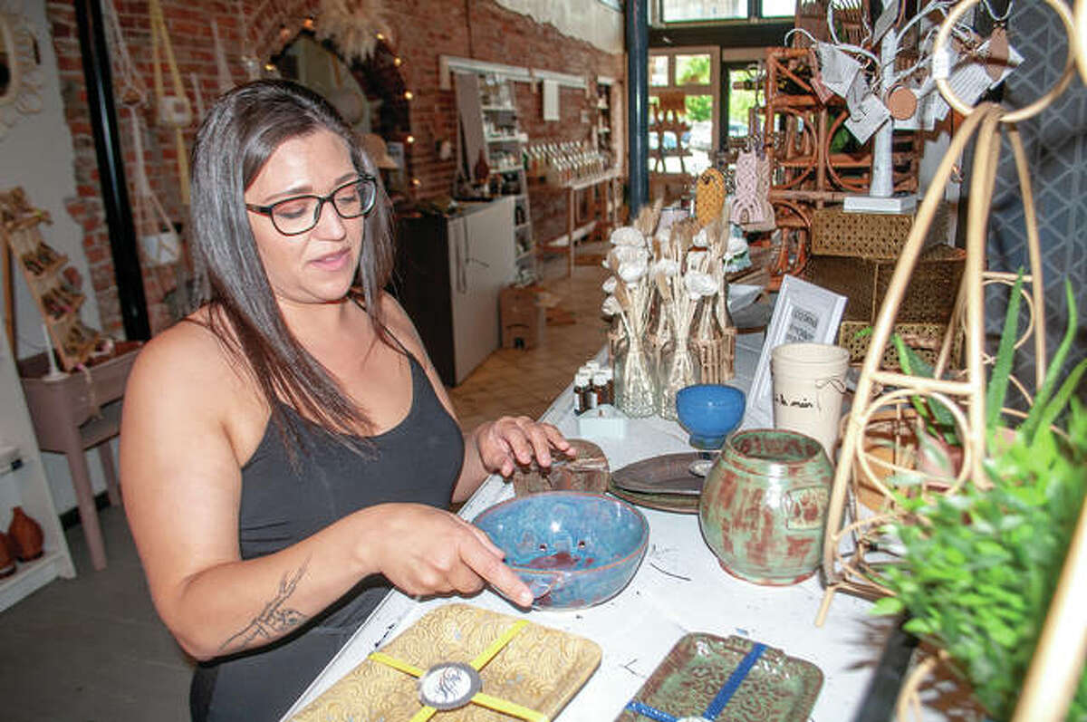 """Anna Myszka, owner and operator of Klarhet Pottery, sets up a display showcasing her work Tuesday afternoon at Green Haven, 66 E. Central Park Plaza. Myszka, a 2012 graduate of MacMurray College, also teaches pottery. """"Klarhet"""" is Norwegian for """"clarity""""."""