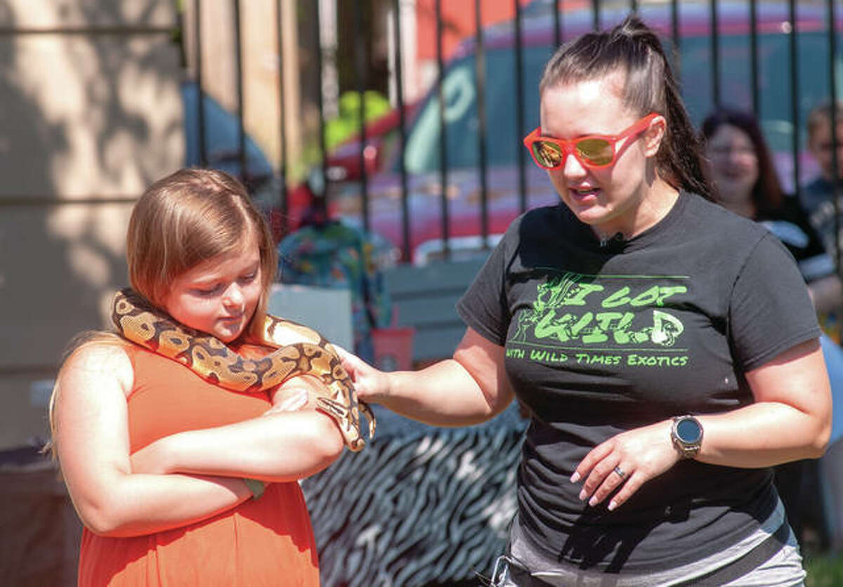 Alyssa Purdue (left), 9, holds a ball python Tuesday morning as Lacey Wild talks about the snake's habits. Wild Times Exotics were at Jacksonville Public Library, talking about wild animals and the importance of being friendly to all creatures. The program also featured a ferret, a kinkajou, a skinny pig, a vinegaroon and a tarantula.