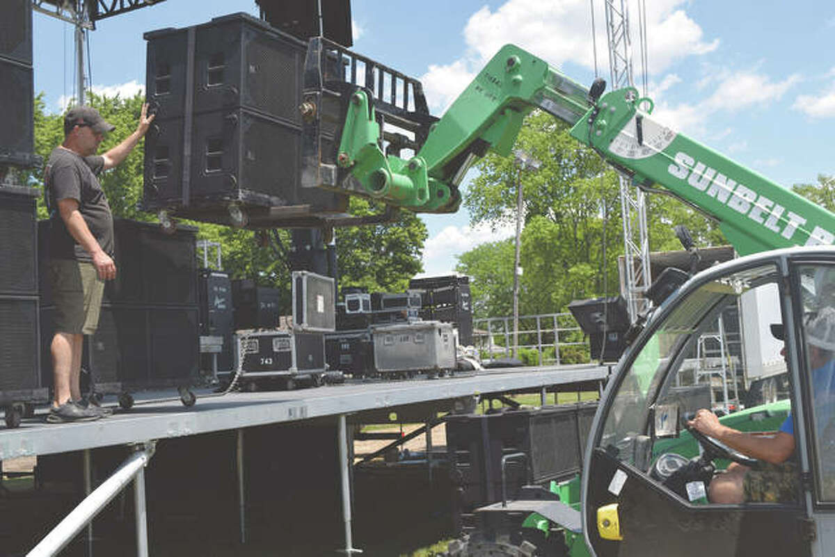 Jason Hebron (left) of Mason Sound works Tuesday on setting the stage at the Sangamon County Fairgrounds in New Berlin ahead of the fair's live concerts, which start tonight.