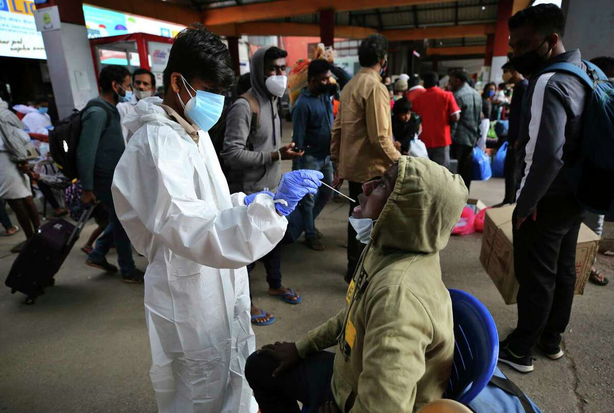 A health worker in protective suit collects a swab sample of a traveler to test for COVID-19 outside a train station in Bengaluru, India, Wednesday, June 16, 2021.