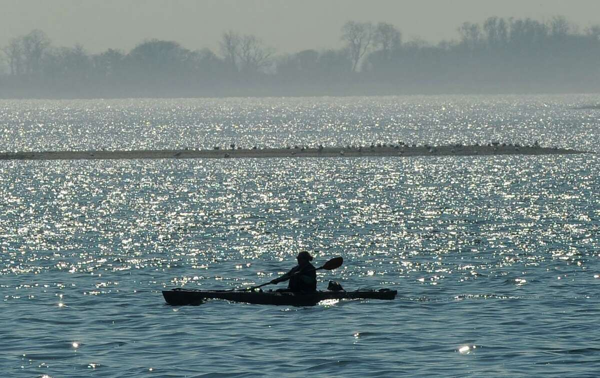 A kayaker paddles along the shoreline of Calf Pasture Beach during in Norwalk.