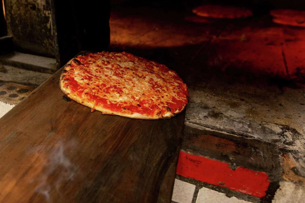 Hot pizza being pulled out of the oven at Sally's Apizza in New Haven.