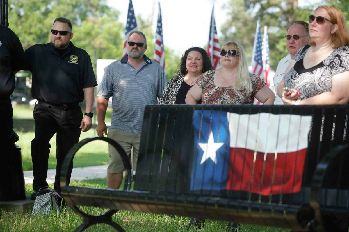 Catherine Dominguez, second from left, listens as two Texas-themed benches are unveiled in honor of her parent's contributions to Cedar Brake Park, Tuesday, June 15, 2021, in Montgomery.