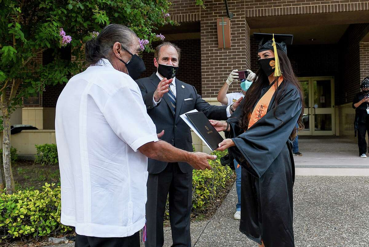 Laredo College BSN graduate Jocelyn De La Cruz receives her diploma from LC District Board of Trustee Dr. Henry Carranza and LC President Ricardo Solis, Tuesday, Jun 30, 2020, outside the college's Guadalupe and Lilia Martinez Fine Arts Center.