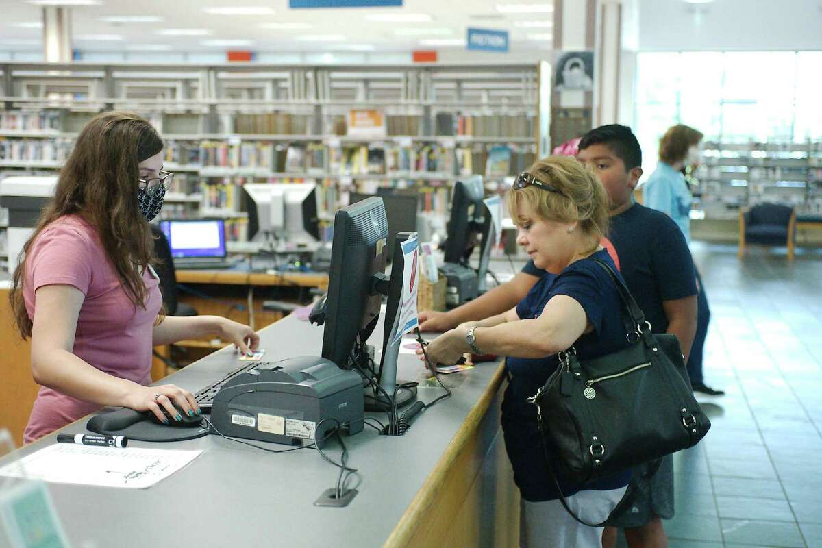 Alvin Library clerk Tracy Gonzales assists Annie Torres and A.J. Perez with new library cards. Branch manager Jennifer Trusty says the staff has seen a marked increase in the number of first-time adult library-card holders.