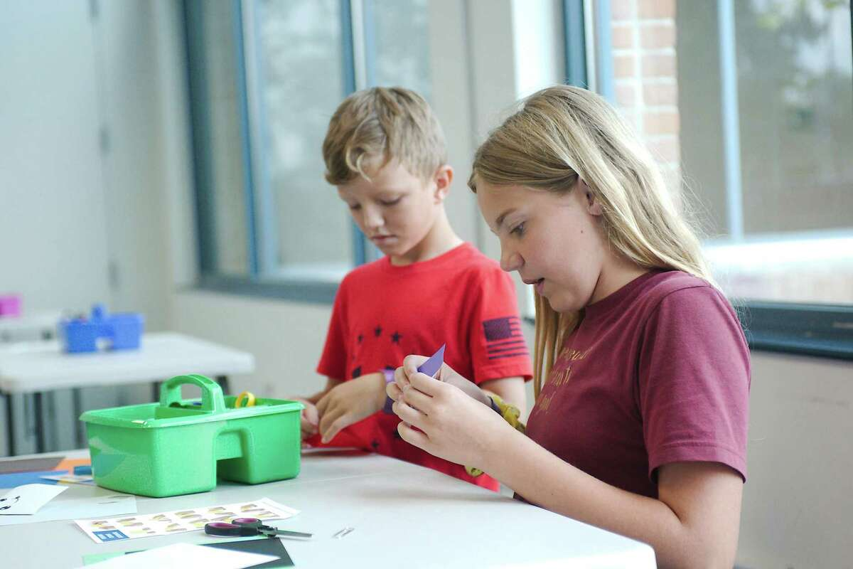Levi Sanders and Addie Ledbetter work on an origami project at the Alvin Library.