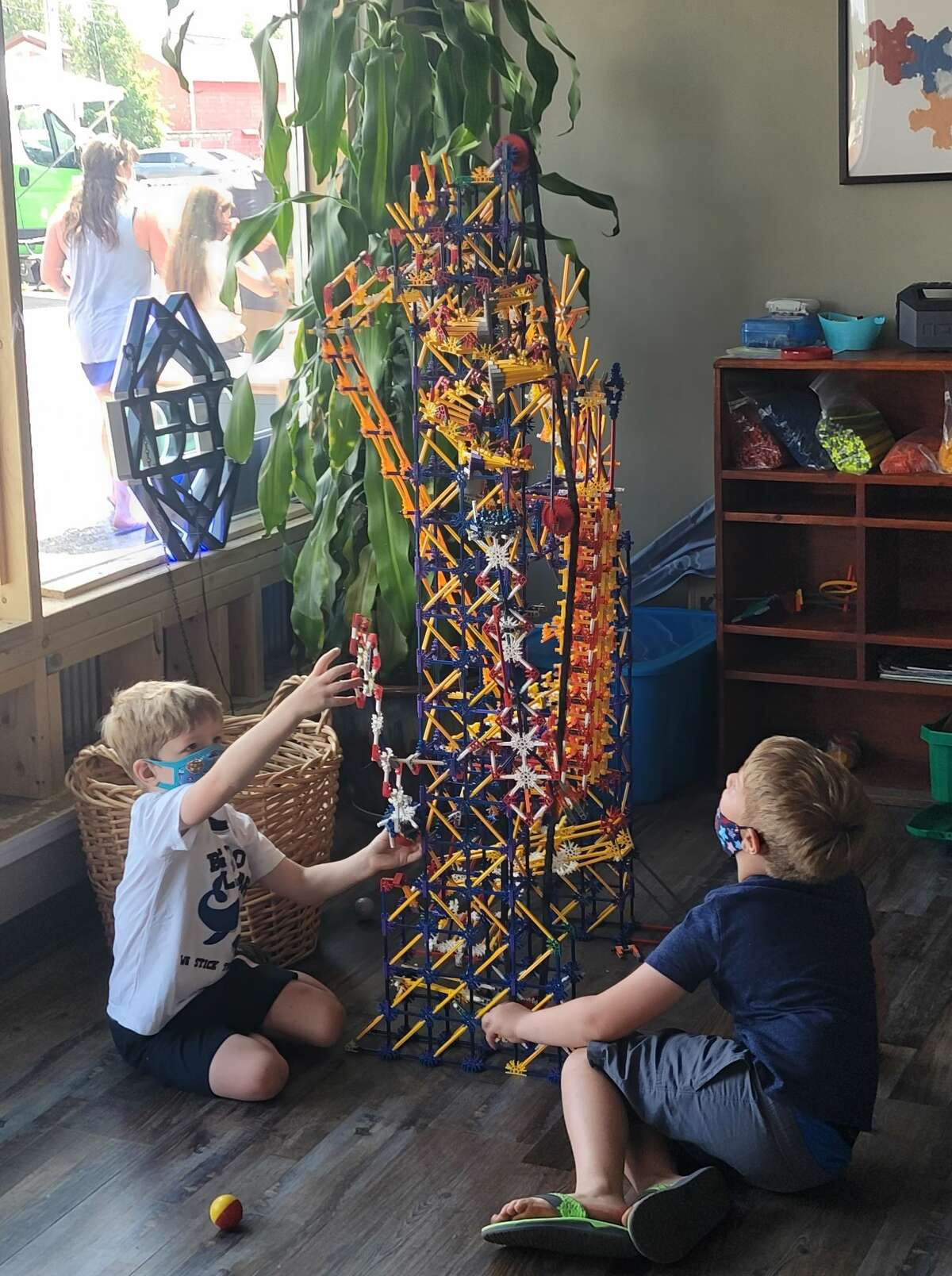 Children work on building a tower with an erector set type of building toy.