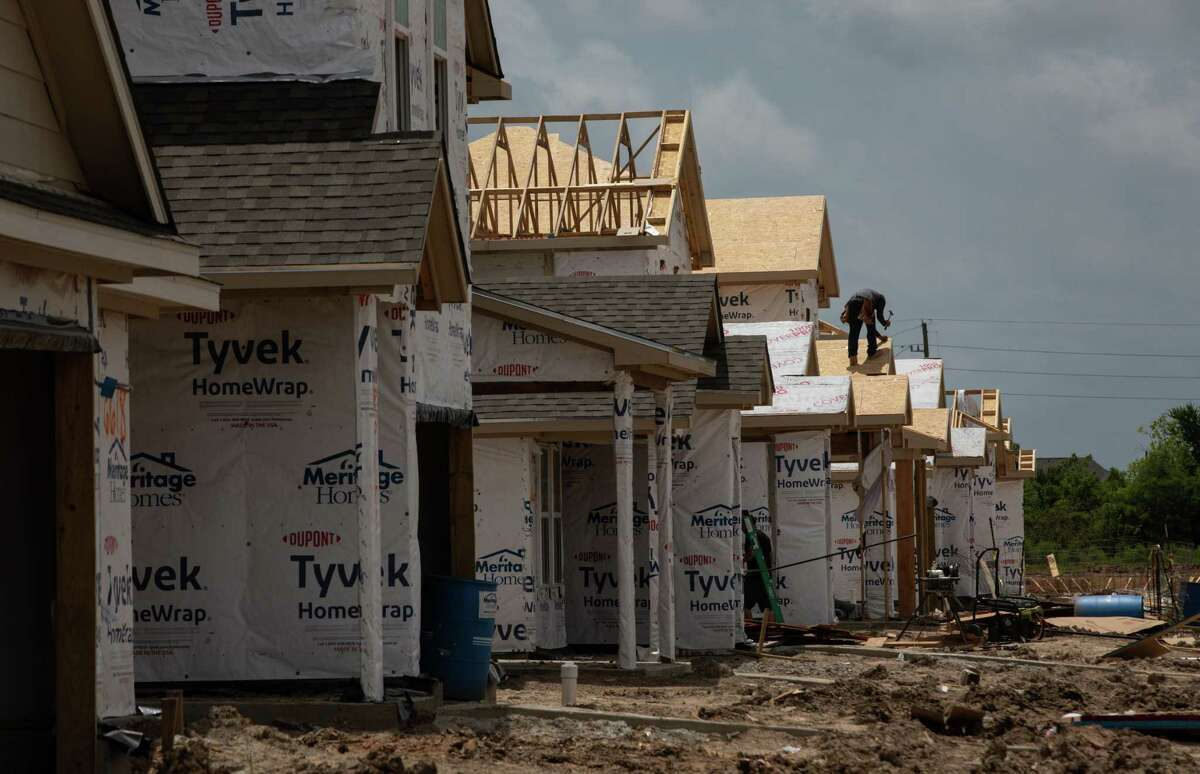 A man works on a roof in the Grand Trails subdivision in Richmond. The average home price shot up to $380,233 in August, up 14 percent from August 2020, according to the Houston Association of Realtors.