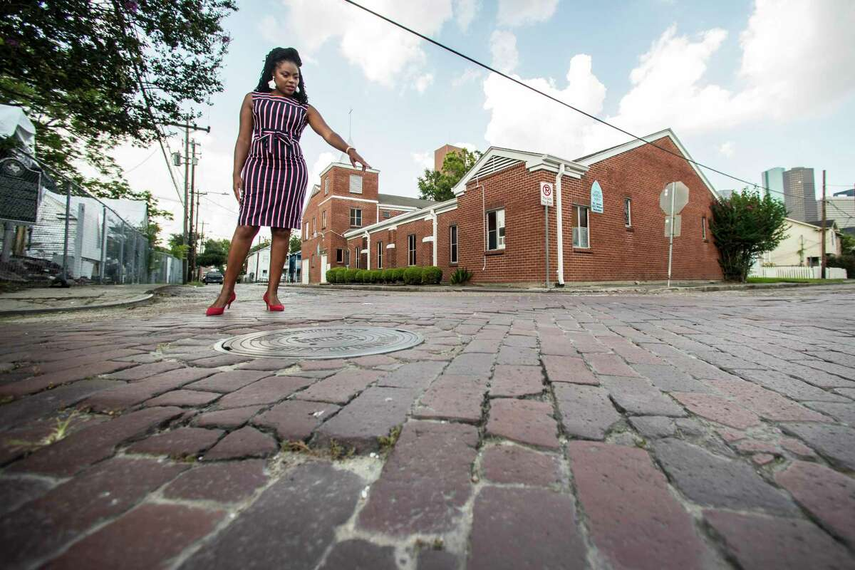 Zion Escobar, executive director of Houston Freedmen's Town Conservancy, stops to take a look at some of the original brick streets in Freedman's Town Tuesday, June 15, 2021 in Houston. Houston City Council is voting Wednesday whether to designate Freedmen's Town a Heritage District, permitting nonprofits to fund improvements in the district. Repairing the brick streets would be one of the top goals of the group.